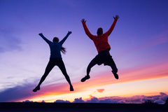 Happy man and woman having fun jumping into air stock images