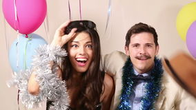 Happy man and woman having a great time in party photo booth. Happy young man and woman having a great time in party photo booth stock video