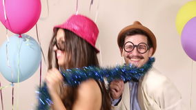 Happy man and woman having a great time in party photo booth stock video