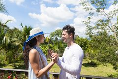 Happy Man And Woman Hodling Hands Stand On Summer Terrace Or Balcony Young Attractive Couple Over Tropical Forest Stock Photos