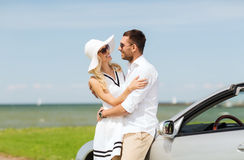 Happy man and woman hugging near car at sea. Transport, travel, love, date and people concept - happy men and women hugging near cabriolet car at sea side Royalty Free Stock Images