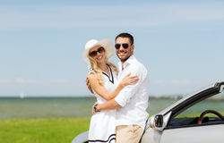 Happy man and woman hugging near car at sea. Transport, travel, love, date and people concept - happy men and women hugging near cabriolet car at sea side Stock Photos