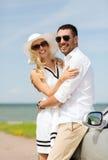 Happy man and woman hugging near car at sea Stock Photo