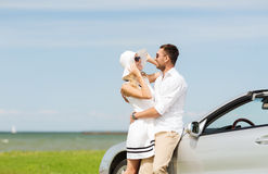 Happy man and woman hugging near car at sea. Transport, travel, love, date and people concept - happy men and women hugging near cabriolet car at sea side Royalty Free Stock Photography