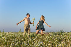 Happy man and the woman jump in the field with camomiles Stock Photo