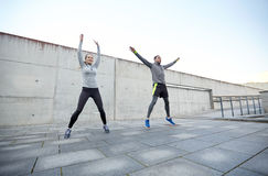 Happy man and woman jumping outdoors Royalty Free Stock Images