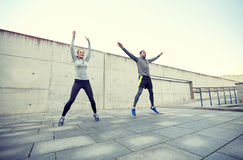 Happy man and woman jumping outdoors Stock Photography