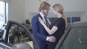 Happy man and woman just bought car in modern motor show. Couple hugging near automobile with opened door in a car stock footage