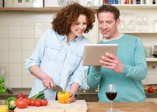 Happy man and woman looking at tablet in the kitchen Royalty Free Stock Images