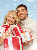 Happy man and woman with many gift boxes Stock Images