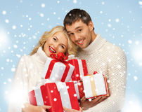 Happy man and woman with many gift boxes Stock Photos