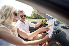 Happy man and woman with map in cabriolet car. Road trip, travel, summer vacation and people concept - happy men and women driving in cabriolet car with map Stock Photo