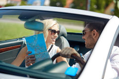 Happy man and woman with map in cabriolet car. Road trip, travel, summer vacation and people concept - happy men and women driving in cabriolet car with map Stock Image