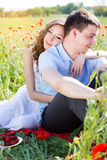 Happy man and woman on a meadow full of poppies Royalty Free Stock Photo