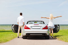 Happy man and woman near cabriolet car at sea Royalty Free Stock Image
