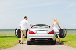 Happy man and woman near cabriolet car at sea Royalty Free Stock Photo