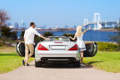 Happy man and woman near cabriolet car in tokyo Royalty Free Stock Images