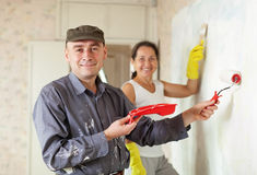 Happy man and woman paints wall at  apartment Stock Images