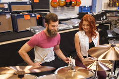 Happy man and woman playing cymbals at music store Stock Photo