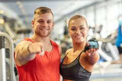 Happy man and woman pointing finger to you in gym. Sport, fitness, lifestyle, gesture and people concept - happy men and women pointing finger to you in gym Royalty Free Stock Images