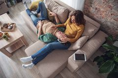 Happy man and woman relaxing in living room stock photography