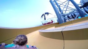 Happy man and woman riding down the water slide. People having fun in water park on resort during summer vacation stock footage
