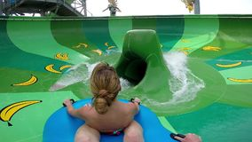 Happy man and woman riding down the water slide. People having fun in water park on resort during summer vacation stock video footage