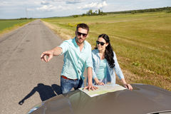 Happy man and woman with road map on car hood Stock Image