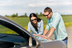 Happy man and woman with road map on car hood Stock Photos