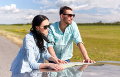 Happy man and woman with road map on car hood Royalty Free Stock Photo