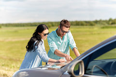 Happy man and woman with road map on car hood Royalty Free Stock Photography