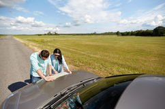 Happy man and woman with road map on car hood Stock Photo