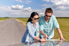 Happy man and woman with road map on car hood Stock Photography