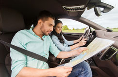 Happy man and woman with road map driving in car Stock Photos