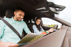 Happy man and woman with road map driving in car Stock Photography