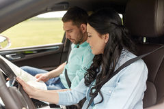Happy man and woman with road map driving in car Royalty Free Stock Photography