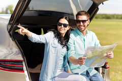 Happy man and woman with road map at hatchback car Royalty Free Stock Photos