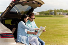 Happy man and woman with road map at hatchback car Stock Image