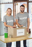 Happy man and woman separating donation stuffs in office Royalty Free Stock Photo