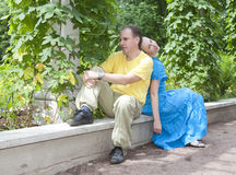 Happy man and the woman sit on a bench in park in the summer Royalty Free Stock Image