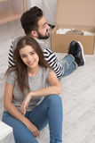 Happy man and woman sitting on the floor tired preparing to relocate to new apartment. Happy men and women sitting on the floor tired preparing to relocate to stock images