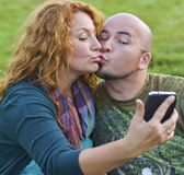Happy man and woman sitting on grass sends kiss to phone Stock Photos