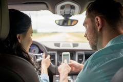 Happy man and woman with smartphone driving in car Stock Photo