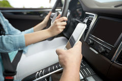 Happy man and woman with smartphone driving in car Royalty Free Stock Photos