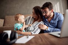 Happy man and woman spending happy time at home with their baby. Happy young men and women spending happy time at home with their baby son and playing together stock photo