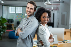 Happy man and woman standing back to back in office. Portrait of happy man and woman standing back to back in creative office Royalty Free Stock Images