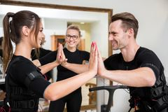 Happy man and woman training together ems exercises. Profile portrait of happy men and women training together ems exercises Stock Photography
