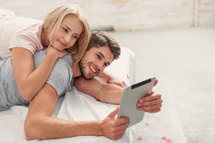 Happy man and woman using computer in bedroom Royalty Free Stock Image