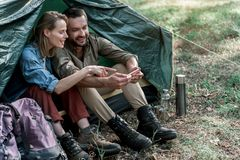 Happy man and woman using phone in the nature. Joyful young loving couple is having rest in forest together. They are sitting in tent and looking at smartphone Royalty Free Stock Photos