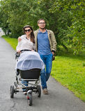 Happy man and woman walking with baby pram Royalty Free Stock Photos